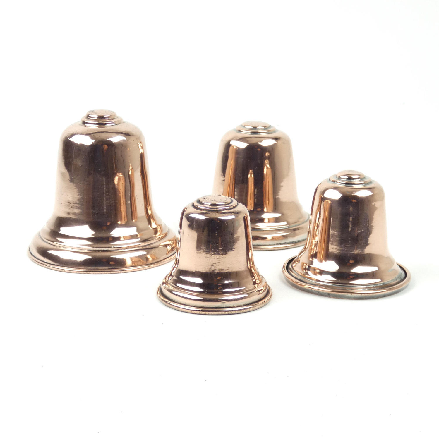 Graduated set of antique copper bell moulds.