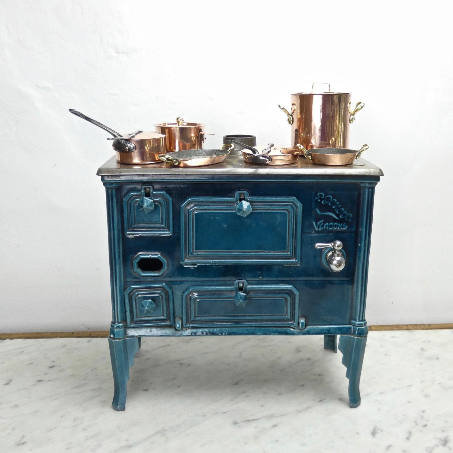 Miniature cast iron, enamelled stove with copper cookware.