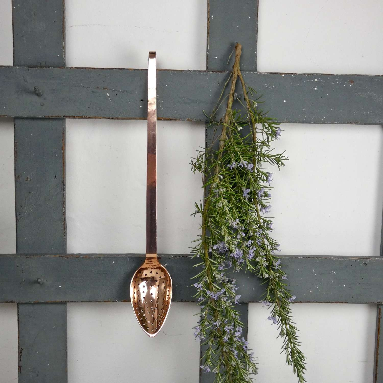 Long, copper straining spoon