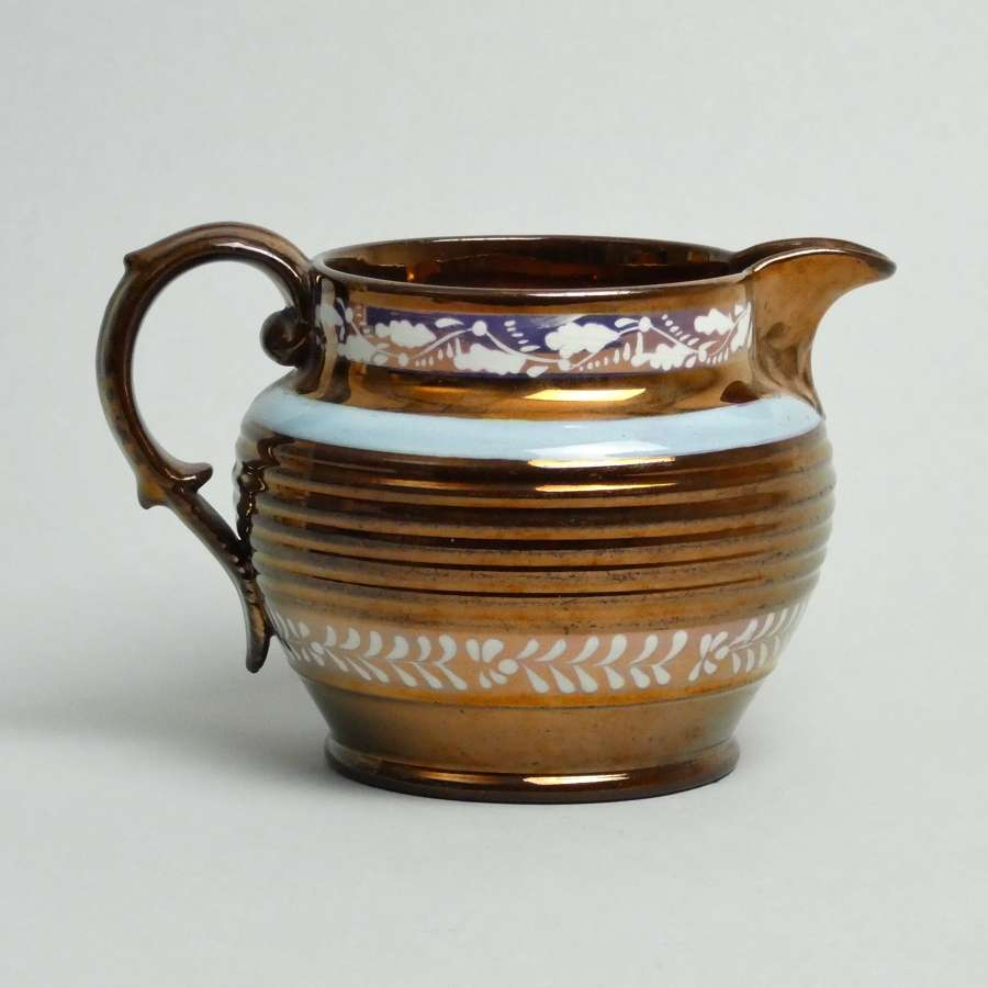 Copper lustre jug with pink resist banding