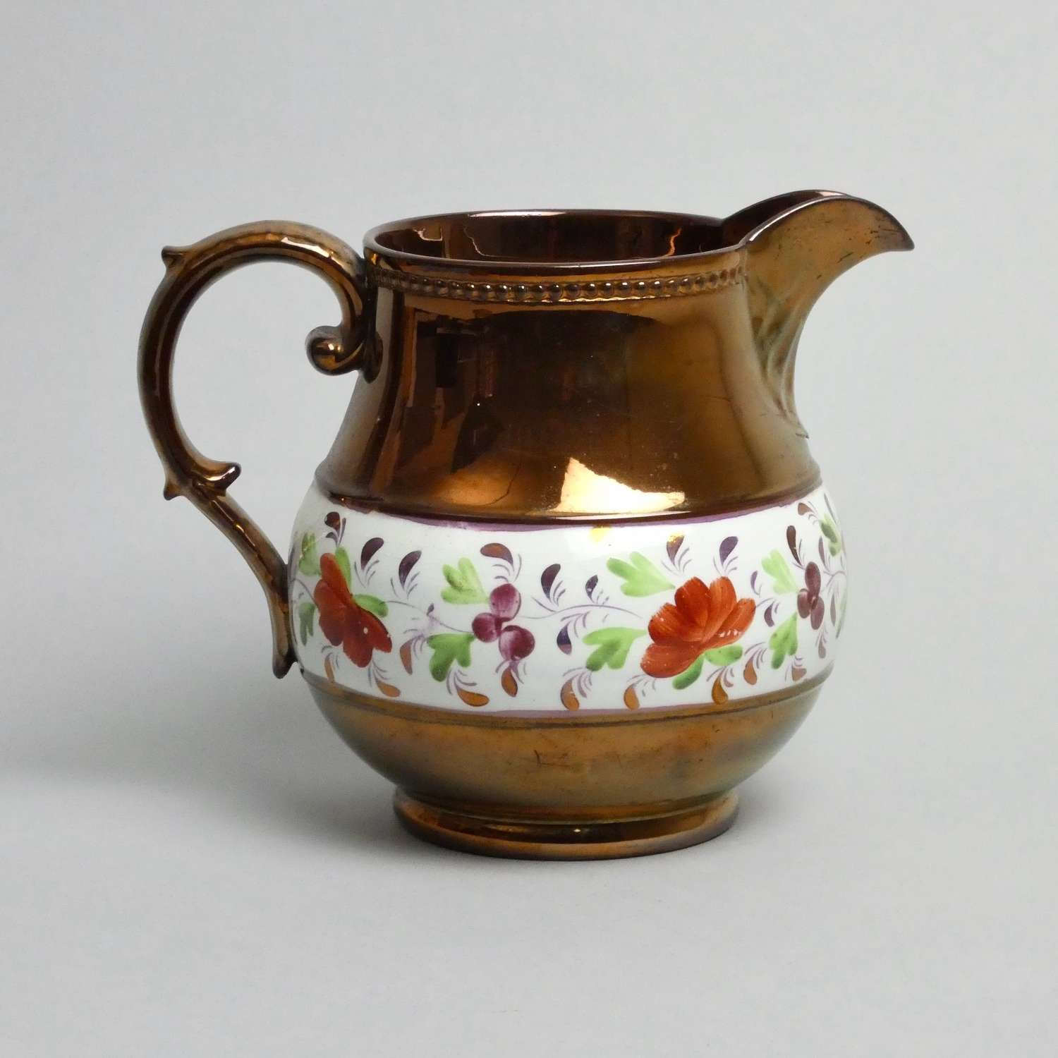 Copper lustre jug with enamelled flowers