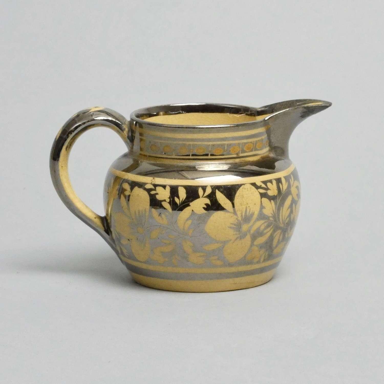 Silver lustre jug on buff ground